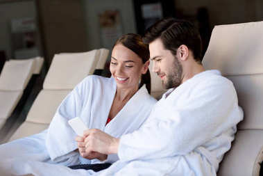 happy young couple in bathrobes using smartphone together while resting in spa center
