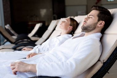 side view of young couple in bathrobes resting together in spa center