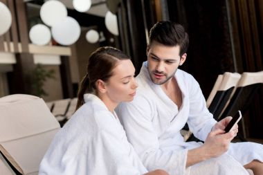 young couple in bathrobes using smartphone together in spa center