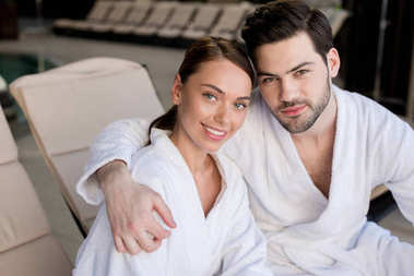 beautiful young couple in bathrobes embracing and smiling at camera in spa center