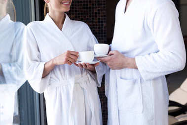 cropped shot of couple in bathrobes drinking tea in spa center