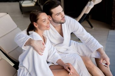 young couple in bathrobes embracing and looking away in spa center
