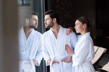 young couple in bathrobes standing together and looking away in spa center