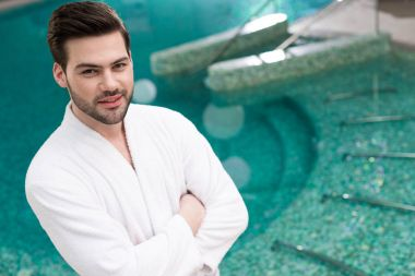 handsome young man in bathrobe standing with crossed arms and looking at camera in spa center