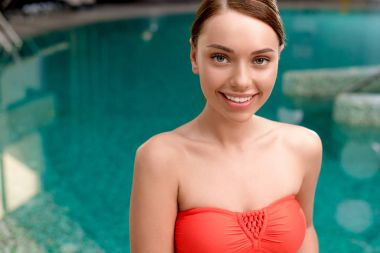 beautiful girl in swimwear smiling at camera while standing near pool in spa center