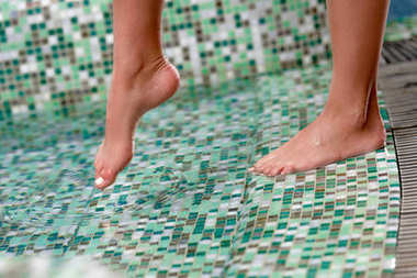 close-up partial view of female feet in pool at spa center