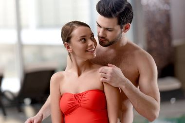 young couple in swimwear smiling each other in spa center