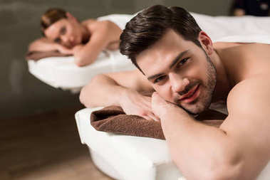 handsome young man looking at camera while having massage in spa salon