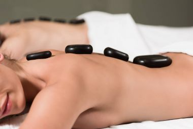 cropped shot of couple receiving hot stones massage in spa center