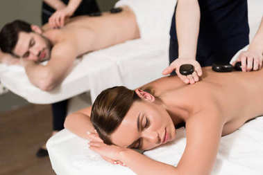 relaxed young couple having hot stones massage in spa center