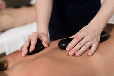 cropped shot of woman having hot stones massage in spa salon
