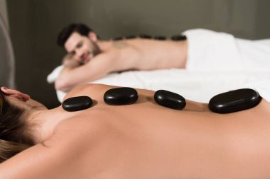 cropped shot of couple looking at each other while having hot stones massage in spa center