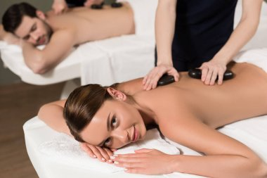 young woman smiling at camera while having hot stones massage