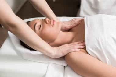young relaxed woman with closed eyes having body massage in spa salon