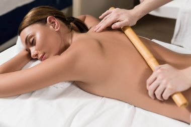 beautiful young relaxed woman having bamboo massage in spa salon