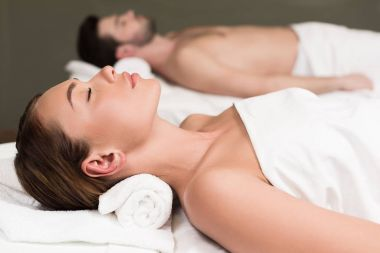 side view of couple with closed eyes lying in spa center