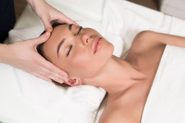 beautiful young woman relaxing and having head massage in spa salon