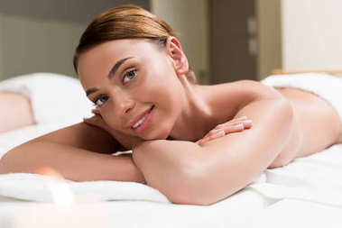 beautiful girl smiling at camera while lying on massage table in spa salon