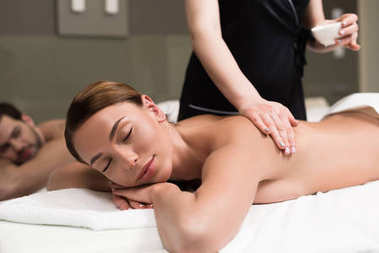 young woman with closed eyes having body massage in spa salon