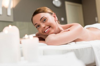 beautiful young woman smiling at camera while lying on massage table in spa salon