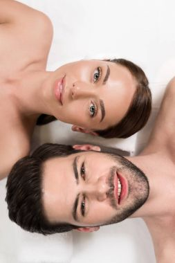 top view of young couple smiling at camera while lying together in spa center