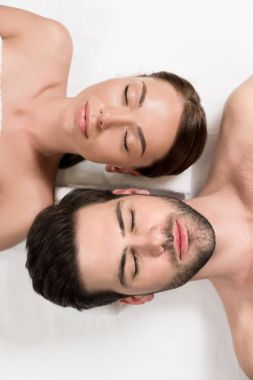 top view of beautiful couple with closed eyes lying together in spa center