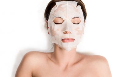 attractive girl in mask on face relaxing with closed eyes in spa salon