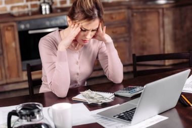 portrait of frustrated woman sitting at table with money, laptop and papers at home, financial problems concept