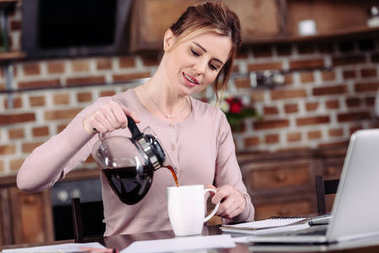 portrait of woman pouring coffee into cup at table with laptop at home
