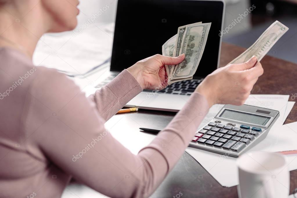 cropped shot of woman counting money at table with laptop