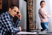 selective focus of argued couple in kitchen at home, financial problems concept