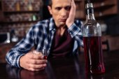 Photo selective focus of depressed man sitting at table with bottle and glass of alcohol at home