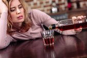 woman pouring alcohol into glass while sitting at table in kitchen
