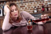 Photo woman pouring alcohol into glass while sitting at table in kitchen