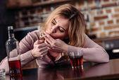 Porträt einer Frau, die Zigarette raucht, während sie zu Hause mit einem Glas Alkohol am Tisch sitzt
