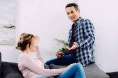 Fotografie boční pohled na muže a ženu bavit při odpočinku na pohovce doma