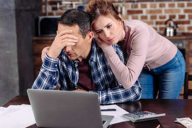 portrait of woman hugging upset husband that sitting at table with laptop at home, financial problems concept