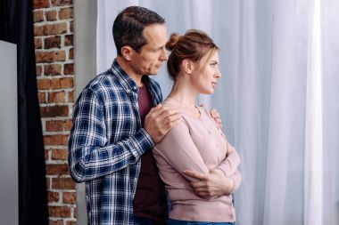side view of man hugging upset wife at home