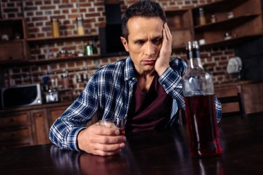 upset man sitting at table with bottle and glass of alcohol at home