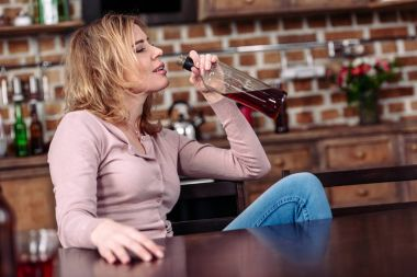 side view of drunk woman with bottle of alcohol sitting at table at home