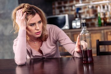 portrait of drunk woman looking at bottle of alcohol on table at home