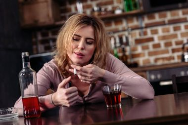 portrait of woman with cigarette and glass of alcohol on table in kitchen