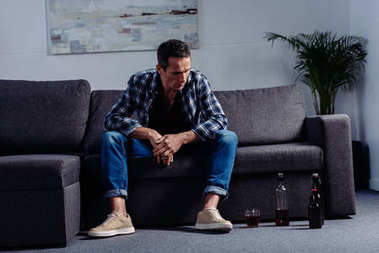 man looking at alcohol on floor while sitting on sofa at home