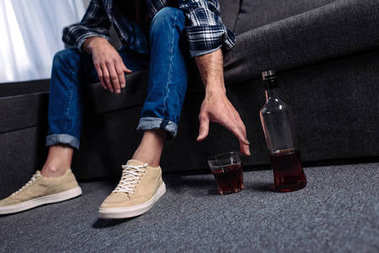 partial view of man taking alcohol drink while sitting on sofa at home