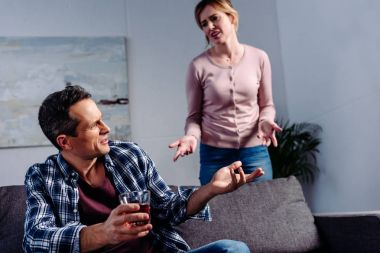 man with glass of alcohol sitting on sofa while arguing with wife behind at home