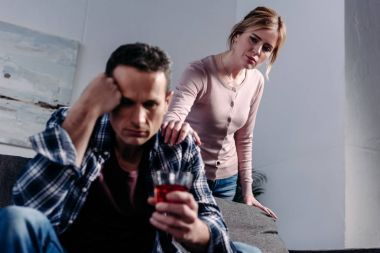 man with glass of alcohol sitting on sofa while wife standing behind at home