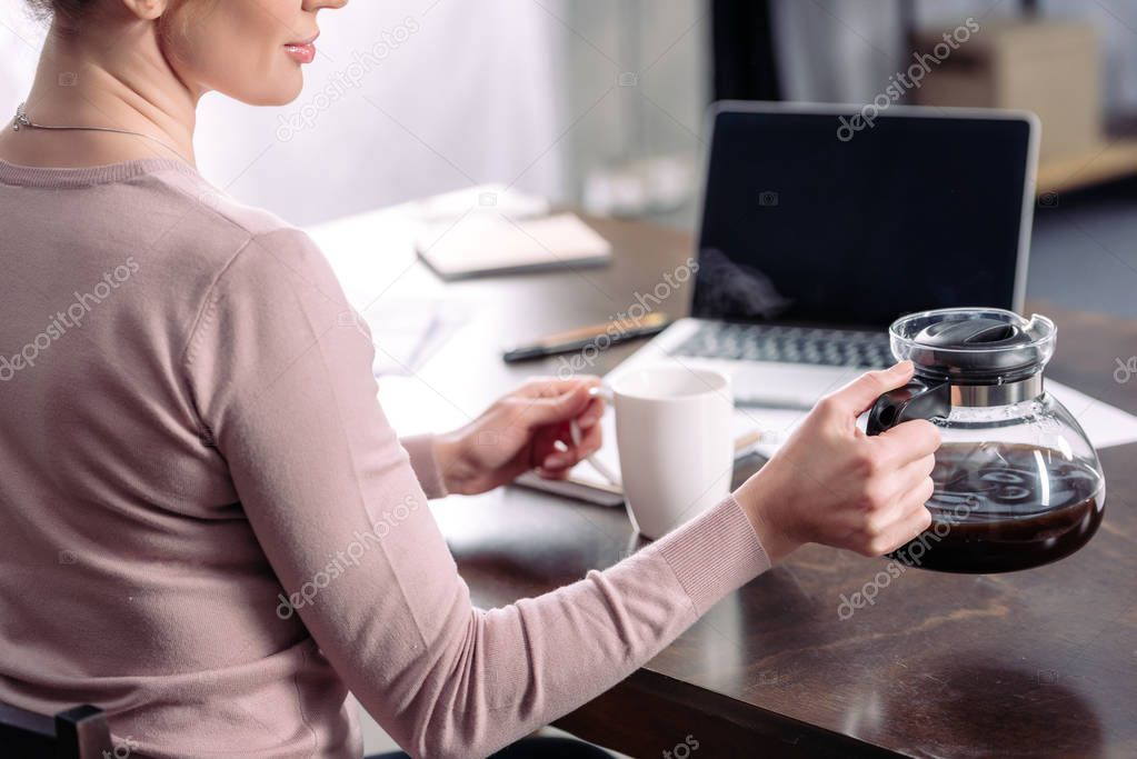 partial view of woman with cup and coffee maker sitting at table with laptop at home