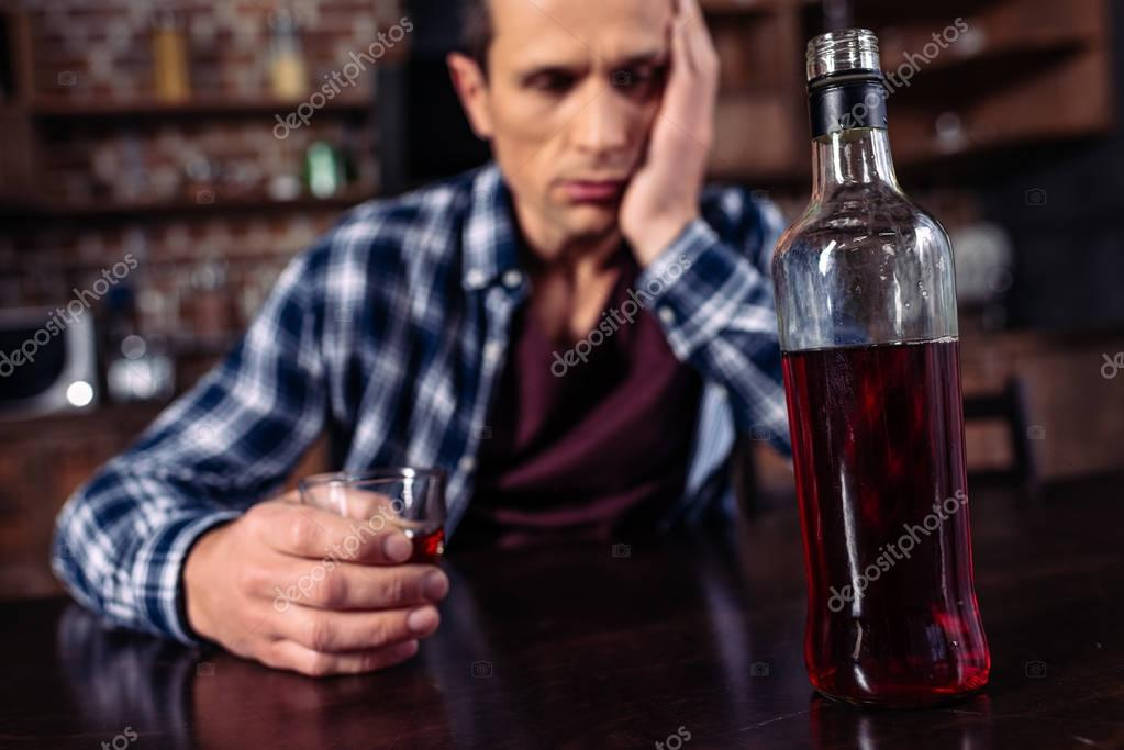 selective focus of depressed man sitting at table with bottle and glass of alcohol at home