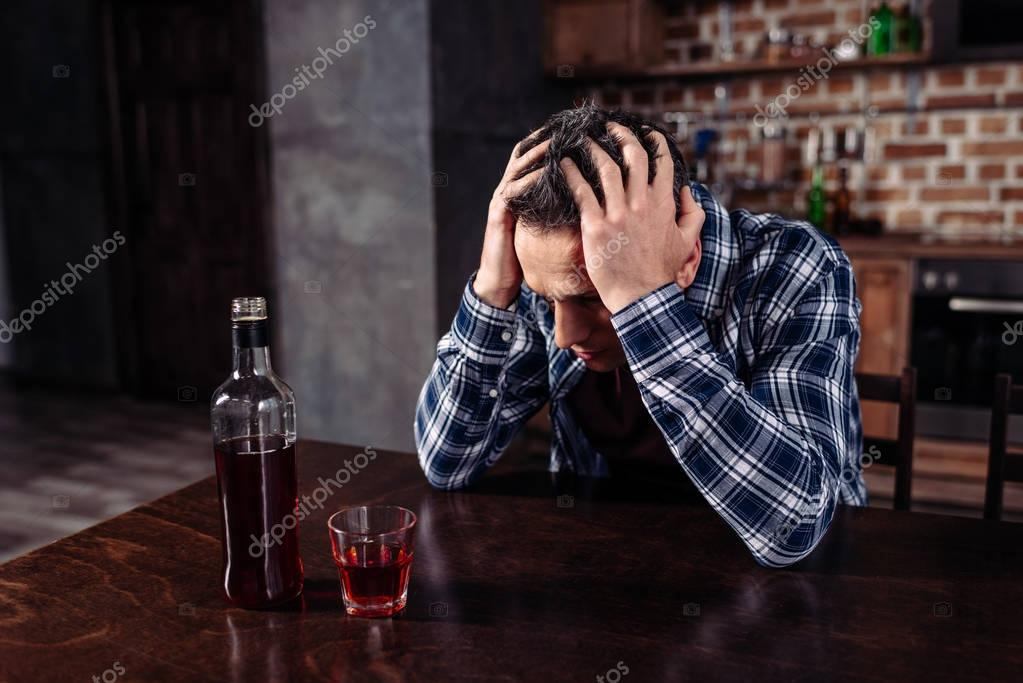 drunk man sitting at table with bottle and glass of alcohol at home