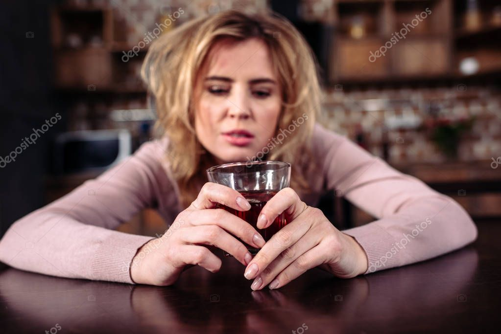 portrait of drunk woman with glass of alcohol sitting t table at home